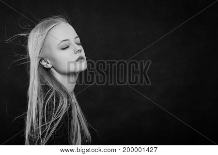 beautiful sensual blond girl on black background on black background with copy space, monochrome