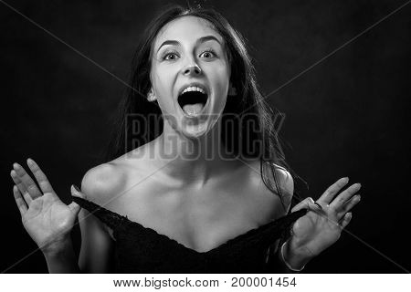 fun young woman undressing on black background, monochrome