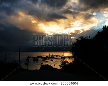 A cloudy Patagonian sunset over the sea. A dramatic scene with a cloudy sky the black pier coming out from orange waters. Black tree silhouette on the right. The picture was taken in Puerto Cisnes Chile