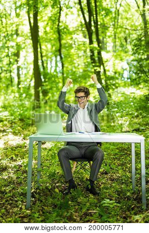 Portrait Of Young Handsome Succesful Business Man In Suit Working At Laptop At Office Table With Rai