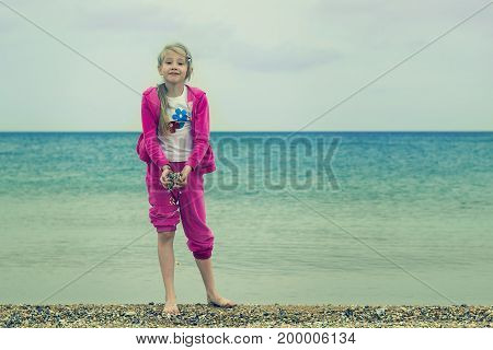 Cheerful girl in a warm suit plays with water in a cold sea. The concept of a happy childhood on the ocean.