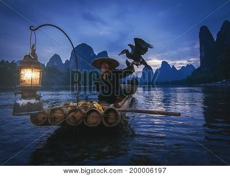 Guilin China; 17th June 2014 - A shot of the famous cormorant taking a smoke break while holding a cormorant bird.