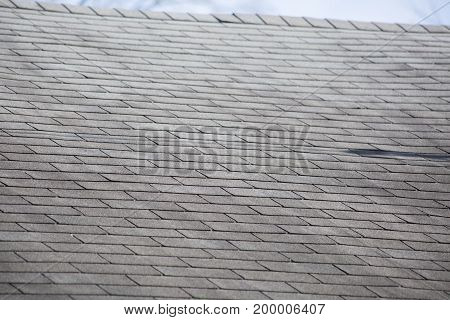 Damaged shingles on a roof after a storm