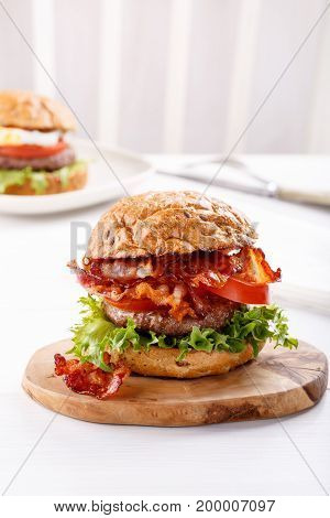 Close-up of beef burger on white background. Hamburger - bun grilled meat burger lettuce tomato and bacon.