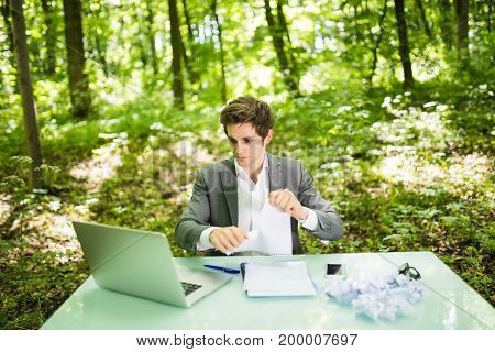 Young Handsome Business Man At Work Table Office With Laptop In Green Forest Tear Work Papers. Busin