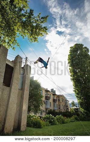 City parkour. The guy does the opposite somersault. Leap from the building. Shooting from the lower angle. Dexterity and extreme.