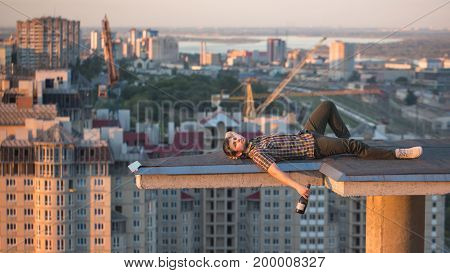 A hipster guy drinks wine from a bottle on the roof of a high-rise building in the city center. He relaxed after a day and is on the roof.