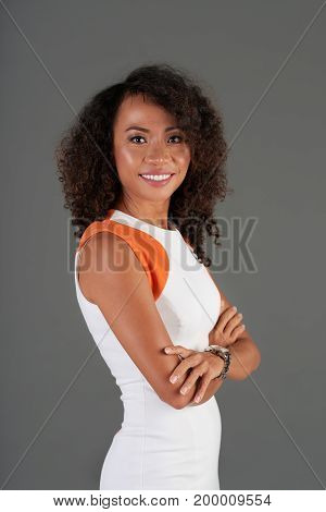 Smiling pretty Asian woman standing with her arms crossed