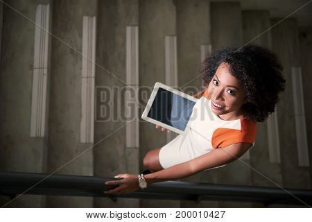 Cheerful business lady with tablet computer standing on the stairs, view from above