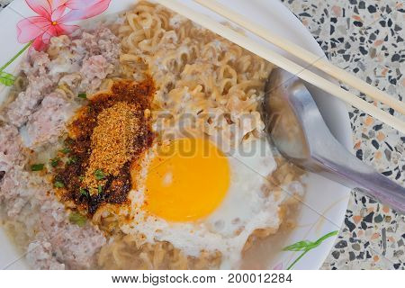 closeup Instant noodles with fresh egg pork and spicy condiment inexpensive just fifteen THB or half US dollar