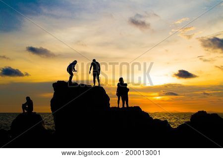 Asian tourists Waiting for sunset On a rock Golden sunlight on the sea and mountains,Nang Phaya Hill Scenic Point thailand