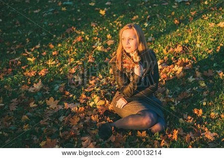 Young beautiful lady with bunch of maple leaves enjoying autumnal sunset. Hope or expectation concept