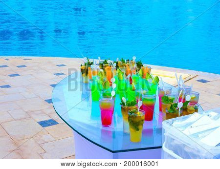 Fruit cocktail glasses at pool - selective focus. Vacation and travel concept