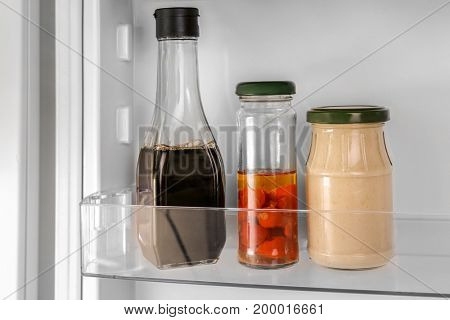 Different sauces on shelf in fridge