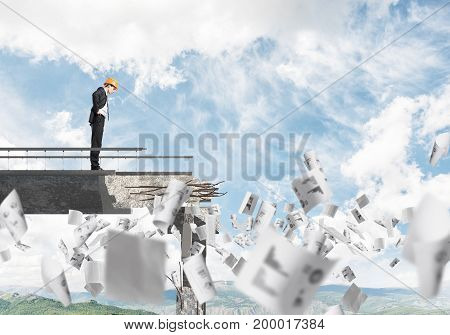 Young engineer in suit and helmet looking down while standing among flying papers on broken bridge with skyscape and nature view on background. 3D rendering.