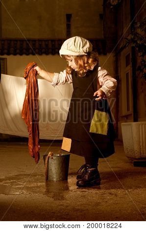 Portrait of a little adorable caucasian girl in character of Cinderella from Charles Perrault's fairy tale does the cleaning. Outdoor photo, emotional portrait. poster