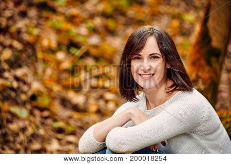 Portrait of cheerful happy young woman on the background of autumn forest