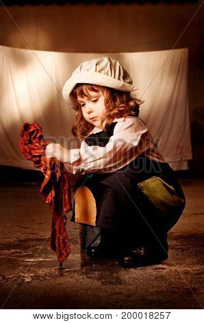 Portrait of a little caucasian girl in character of Cinderella from Charles Perrault's fairy tale does the cleaning. Outdoor photo, emotional portrait.