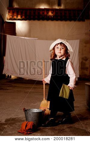 Portrait of a little caucasian girl in costume of Cinderella from Charles Perrault's fairy tale. Outdoor photo.