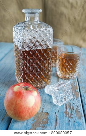 Decanter glasses and apple on the old wooden table. Crockery alcohol exterior