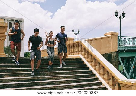 Group of Vietnamese cheerful people running down the stairs