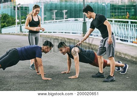 Young people supporting their friends who are doing push-ups