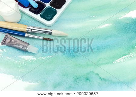 Artistic Paintbrushes And Paints On Green Watercolor Background