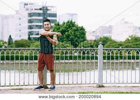 Cheerful handsome Vietnamese young man stretching arms after jogging