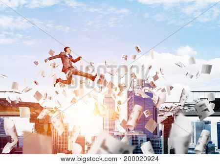 Businessman jumping over gap with flying paper documents in concrete bridge as symbol of overcoming challenges. Cloudly with sunlight skyscape on background. 3D rendering.