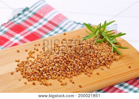 pile of raw buckwheat on wooden cutting board - close up