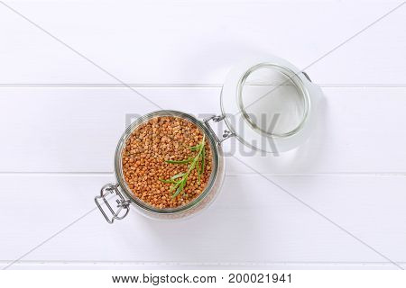 jar of raw buckwheat on white wooden background
