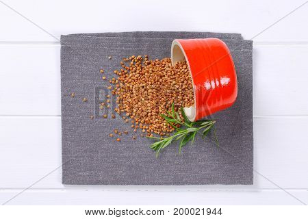 bowl of raw buckwheat spilt out on grey place mat