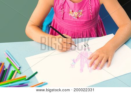 Cropped image of girl drawing with pencils