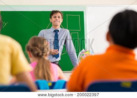 Young smiling teacher explaining new topic to the class