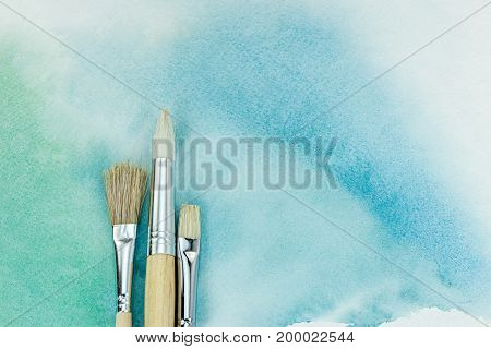 Artist Paintbrushes On Hand Painted Green Watercolor Background