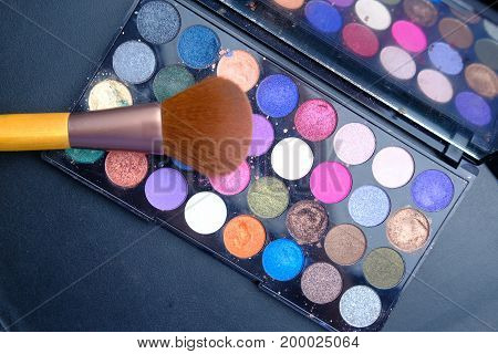 colorful eyeshadows in black boxes and a brushe isolated on black .