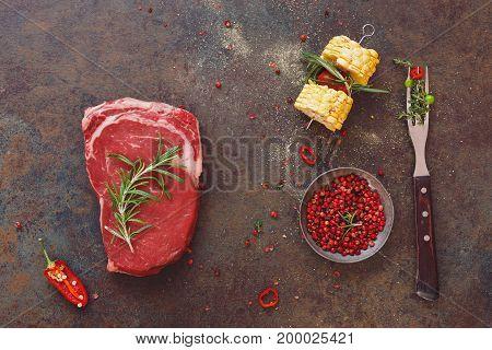 Raw black angus steak with vegetable and seasonings,  preparing food, stone background, top view