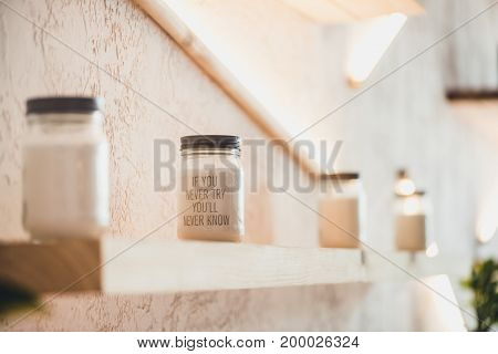 jars with inspiring quote standing in row on shelf