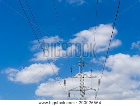 Close-up of Power Lines in front of a blue Sky. View on Power Lines in front of a blue Sky withe Clouds. Natural Backgrounds.