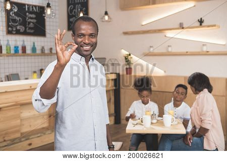 African-american Man Showing Okay Sign With His Family Blurred On Background