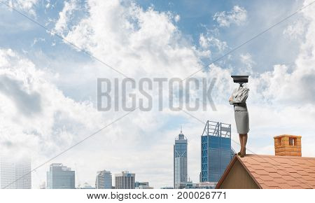 Faceless businesswoman with camera zoom instead of head standing on house roof