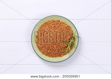 plate of raw buckwheat on white wooden background poster