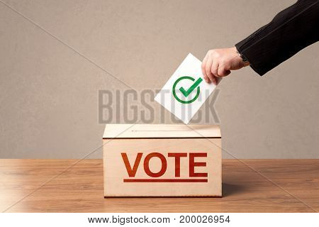Close up of male hand putting vote into a ballot box, on grunge background