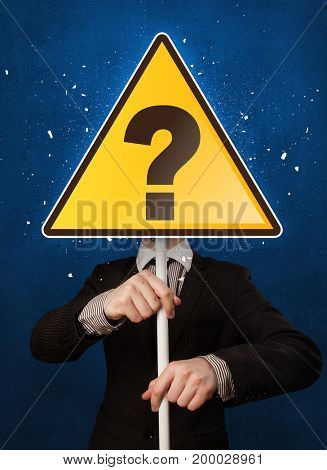 Smart businessman holding yellow sign with question mark