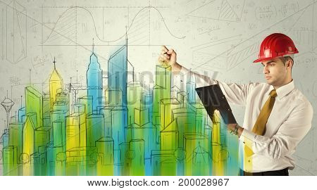 A talented young architect drawing a plan of a future city with blue, green, yellow buildings, churches, including lines and measurements.