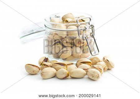 Pistachio nuts in jar isolated on white background. Glass jar with pistachio nuts.