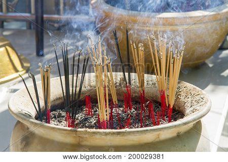 Incense burner with orange incense and black smoke.