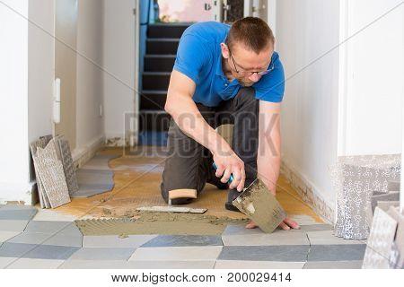 Man Tiling Floor Using Trowel