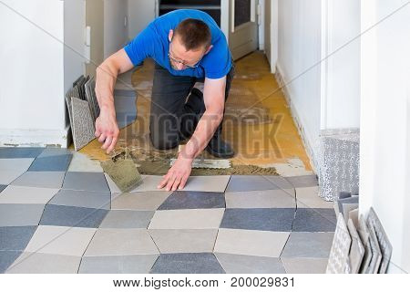 Handyman Laying Tiles In New House