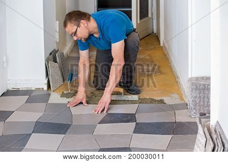 Man Installing Floor Tiles
